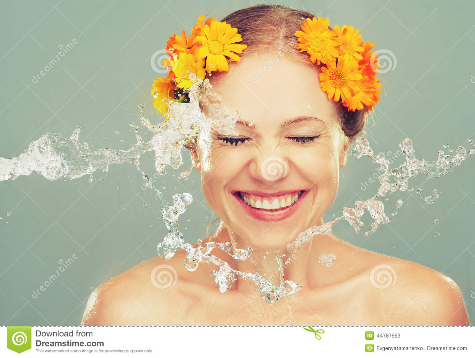 A menina de riso da beleza com espirra da água e de flores amarelas