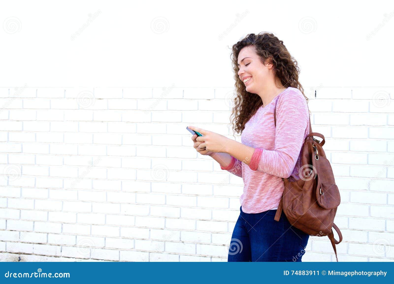 Menina de riso que está e que texting com trouxa