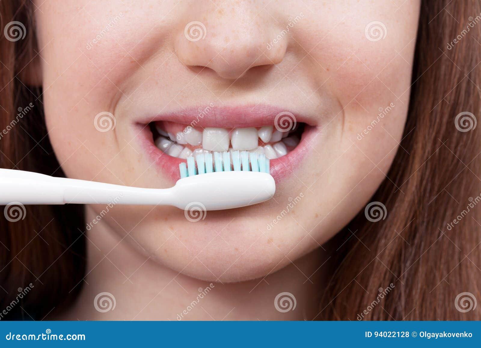 Menina de sorriso bonito que escova seus dentes