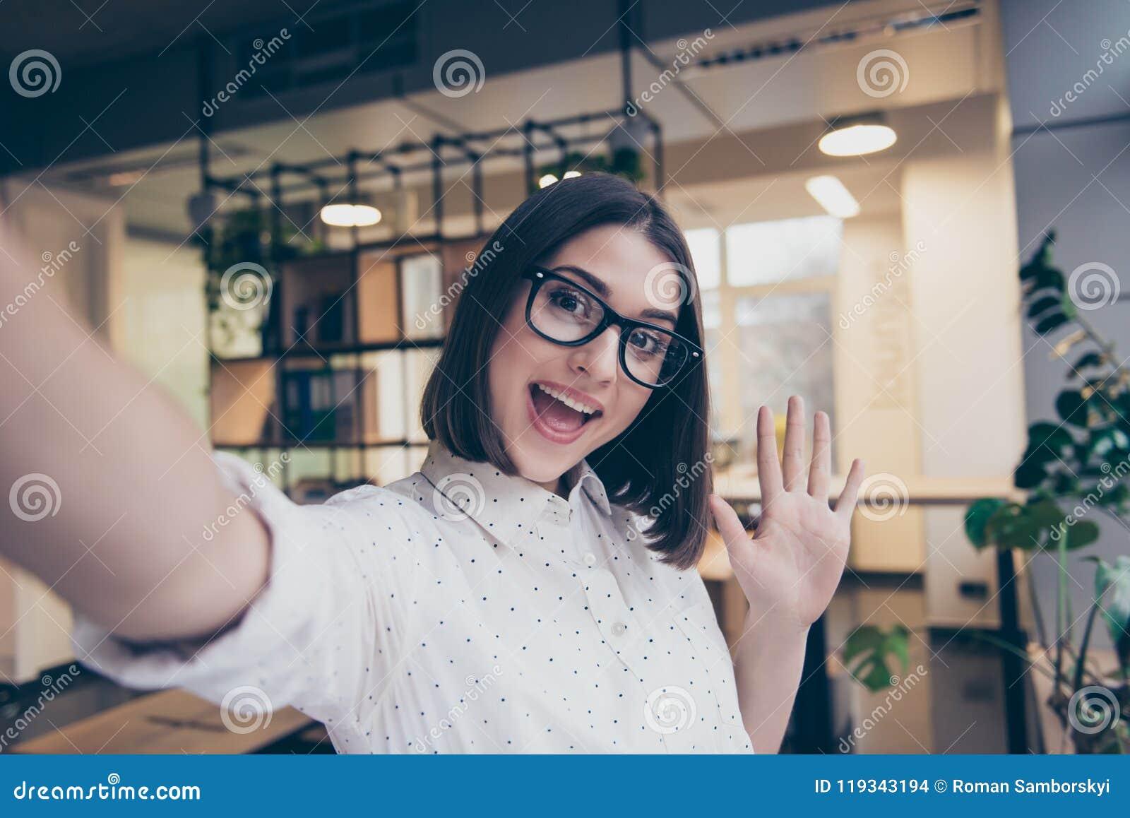 Menina de sorriso consideravelmente nova nos vidros que tomam um selfie que trabalha na estação de trabalho clara do local de tra