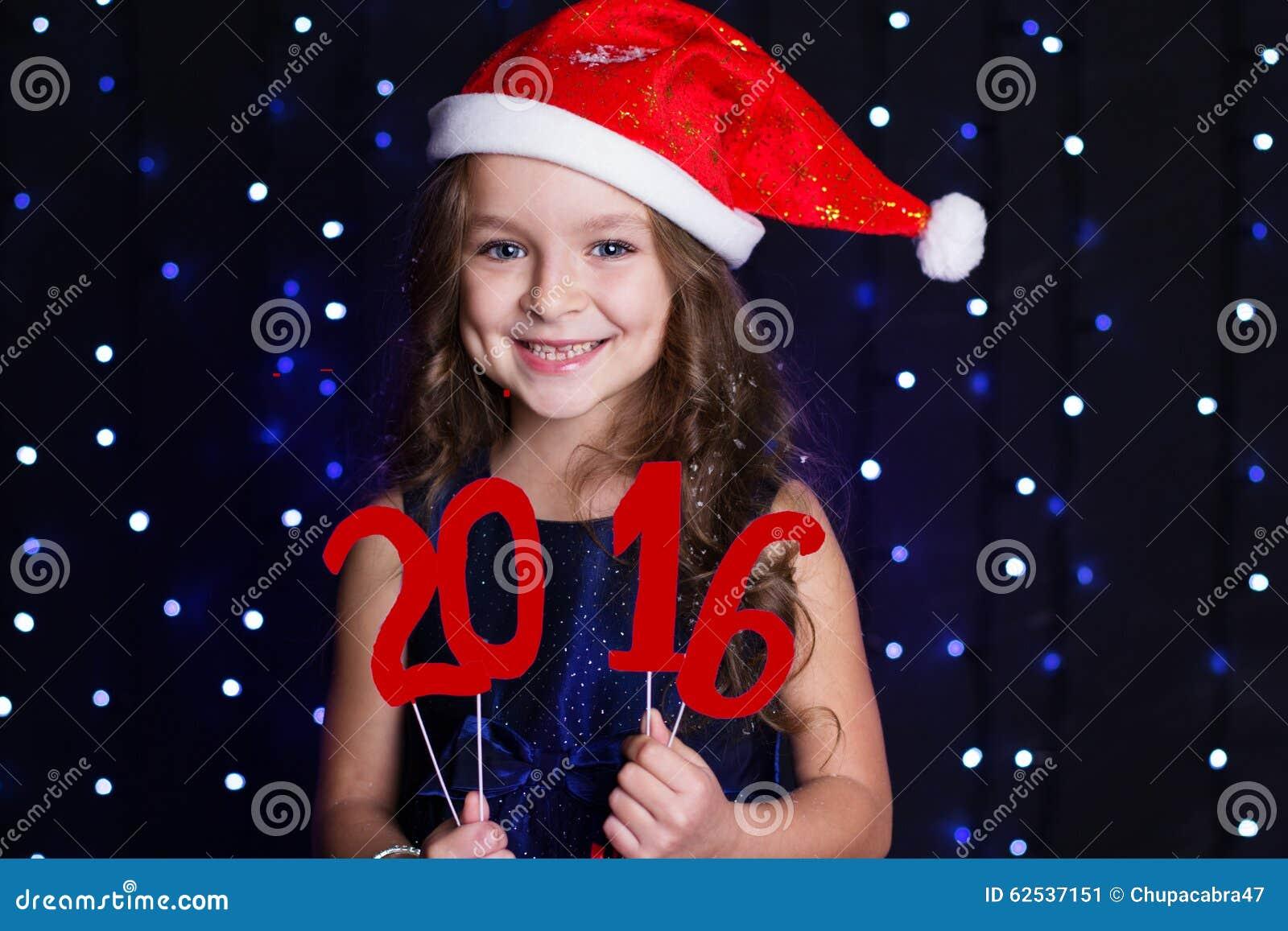 A menina de sorriso de Santa com ano novo vermelho data 2016