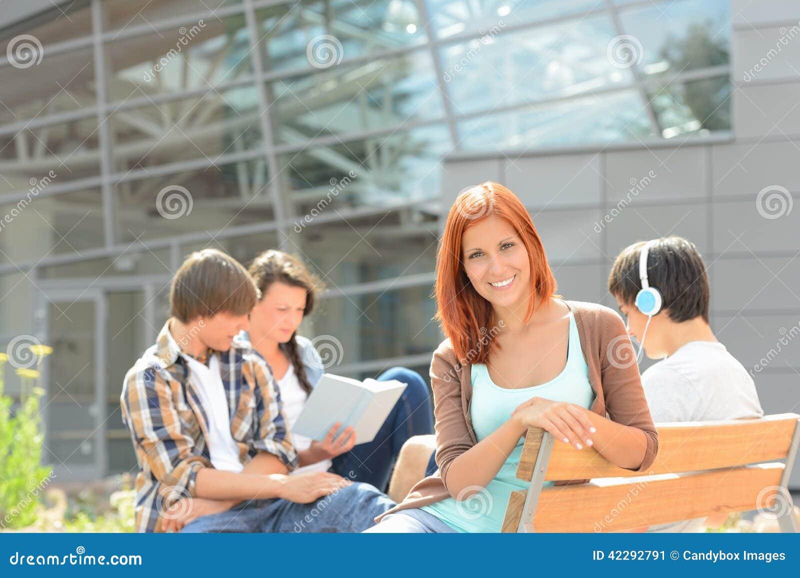 Menina de sorriso do estudante com os amigos fora da faculdade