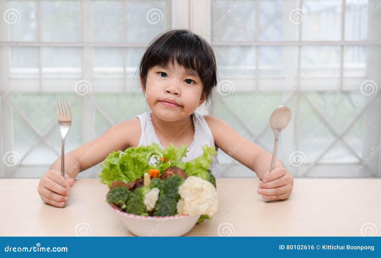 A menina de sorriso doce bonito nova pequena come a salada fresca/conceito saudável comer