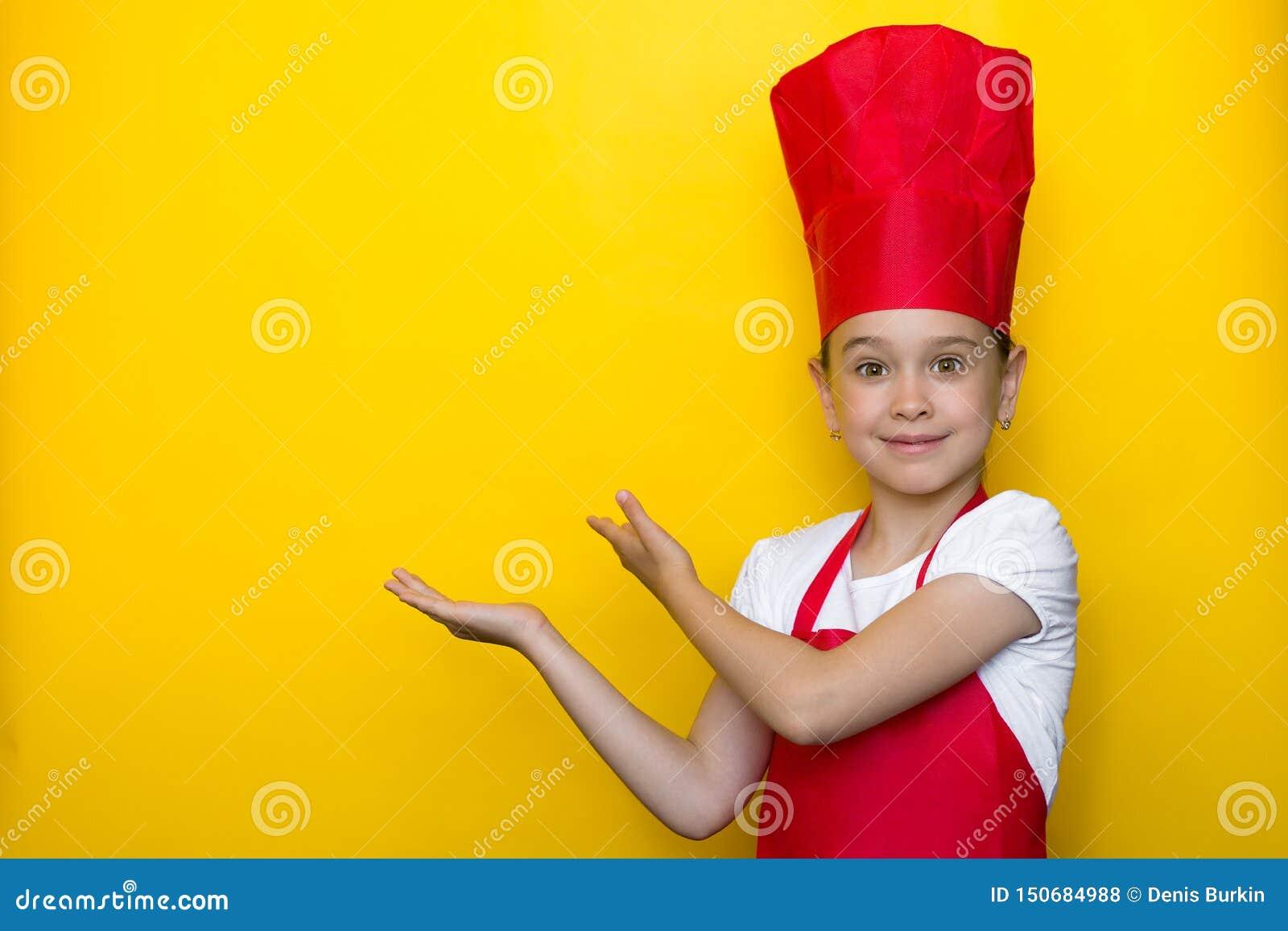 Menina de sorriso em pontos do terno de um cozinheiro chefe vermelho com ambas as mãos a um espaço da cópia em um fundo amarelo