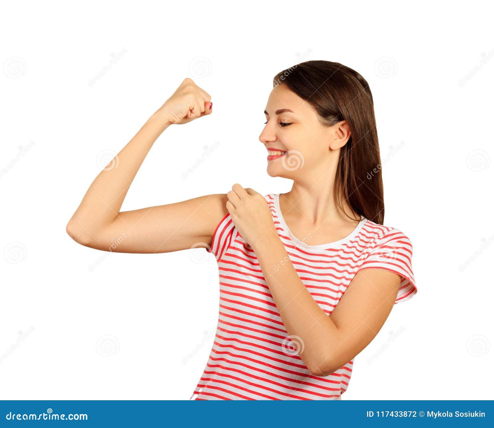 A menina de sorriso está apontando em seu bíceps menina emocional isolada no fundo branco