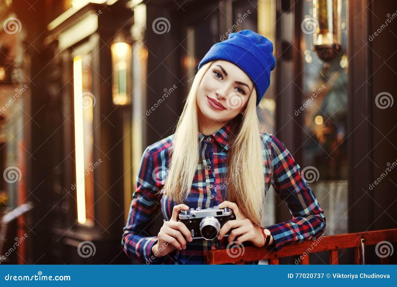 Menina de sorriso feliz à moda do moderno com a câmera retro do vintage Feche acima do retrato da rua toned