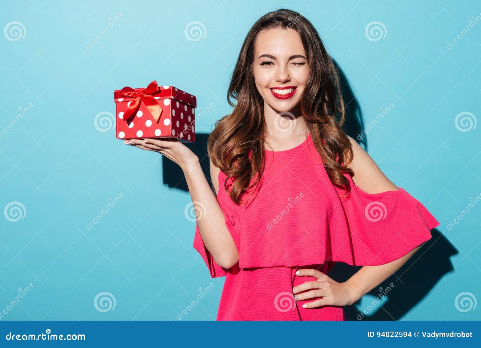 Menina de sorriso feliz no vestido que guarda a caixa atual e pisc