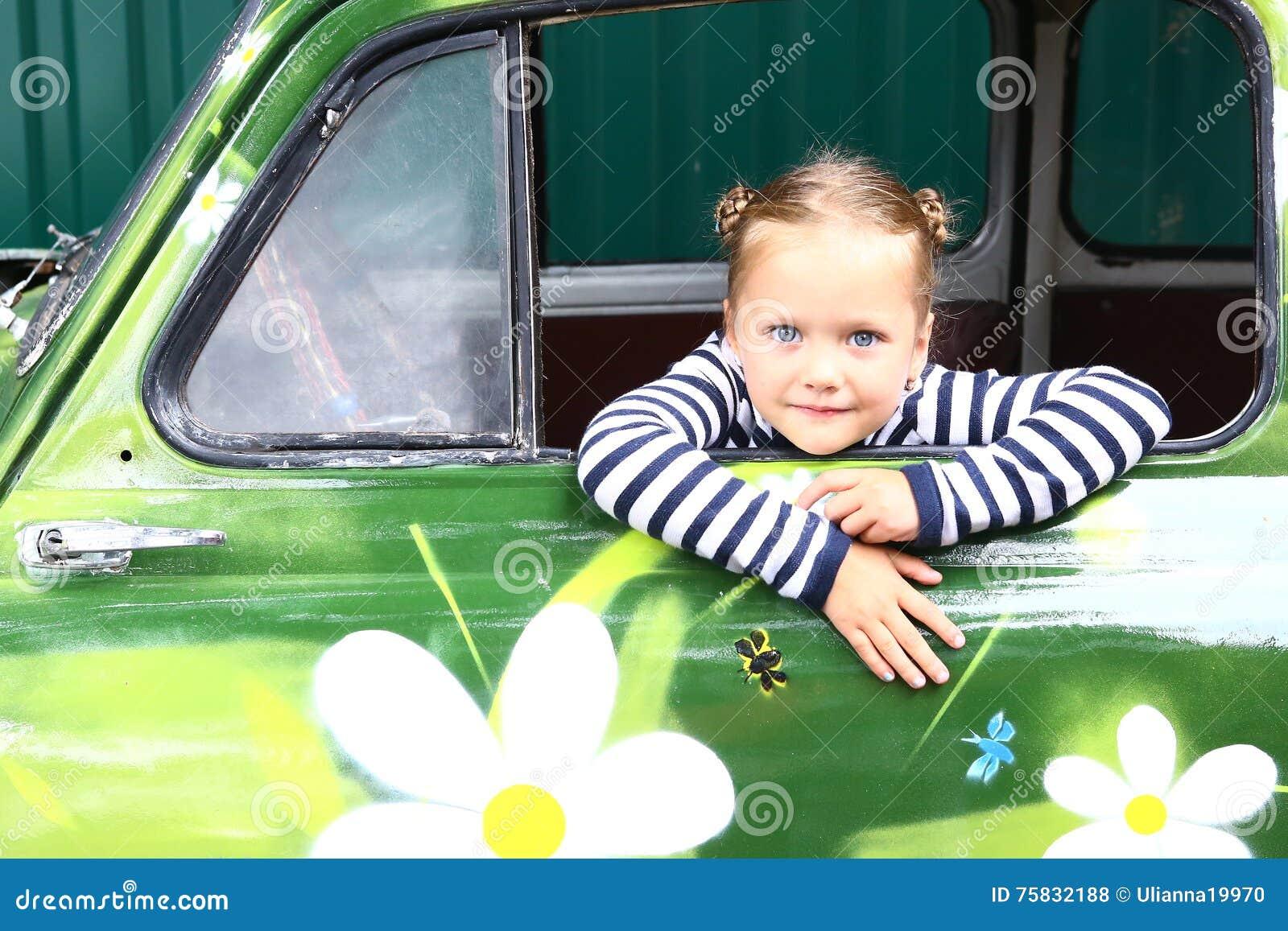 Menina de sorriso loura do preteen no carro pintado velho