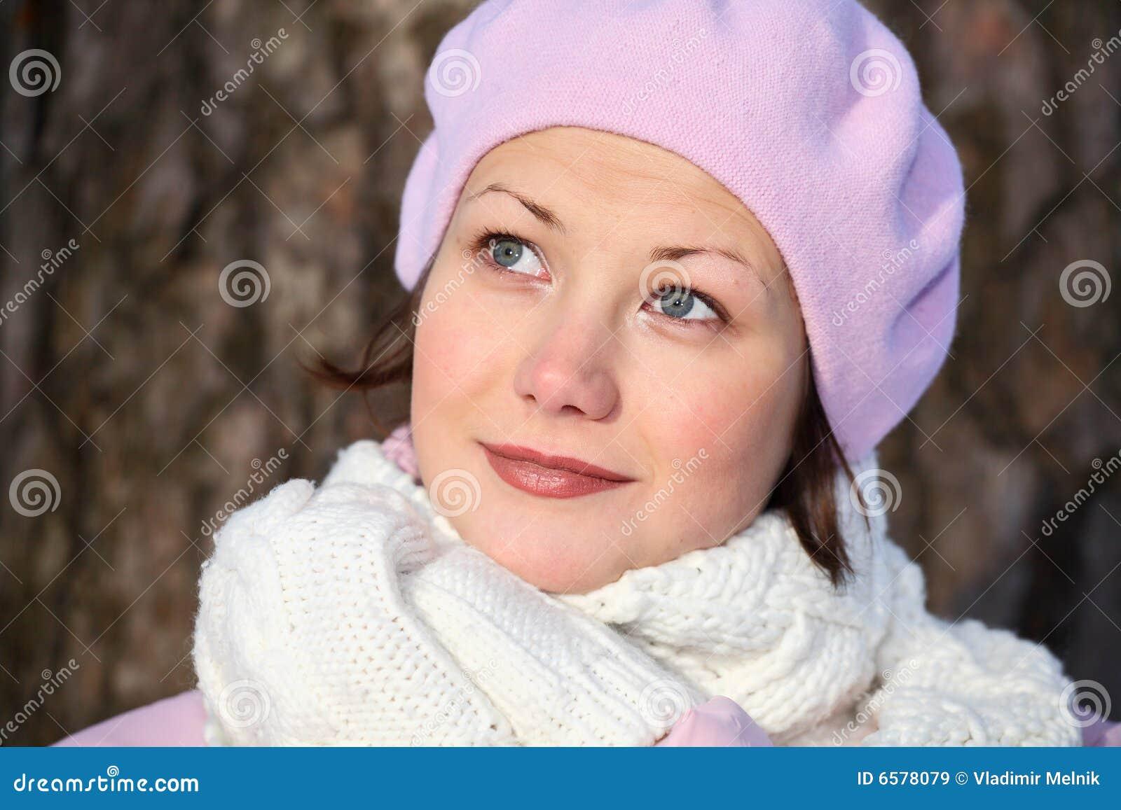 Menina de sorriso na boina cor-de-rosa