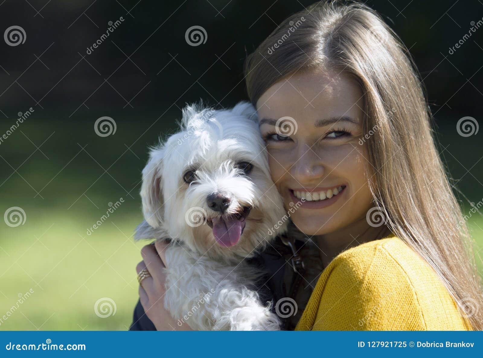 Menina de sorriso no abraço de um cão branco pequeno Um sorriso grande em sua cara