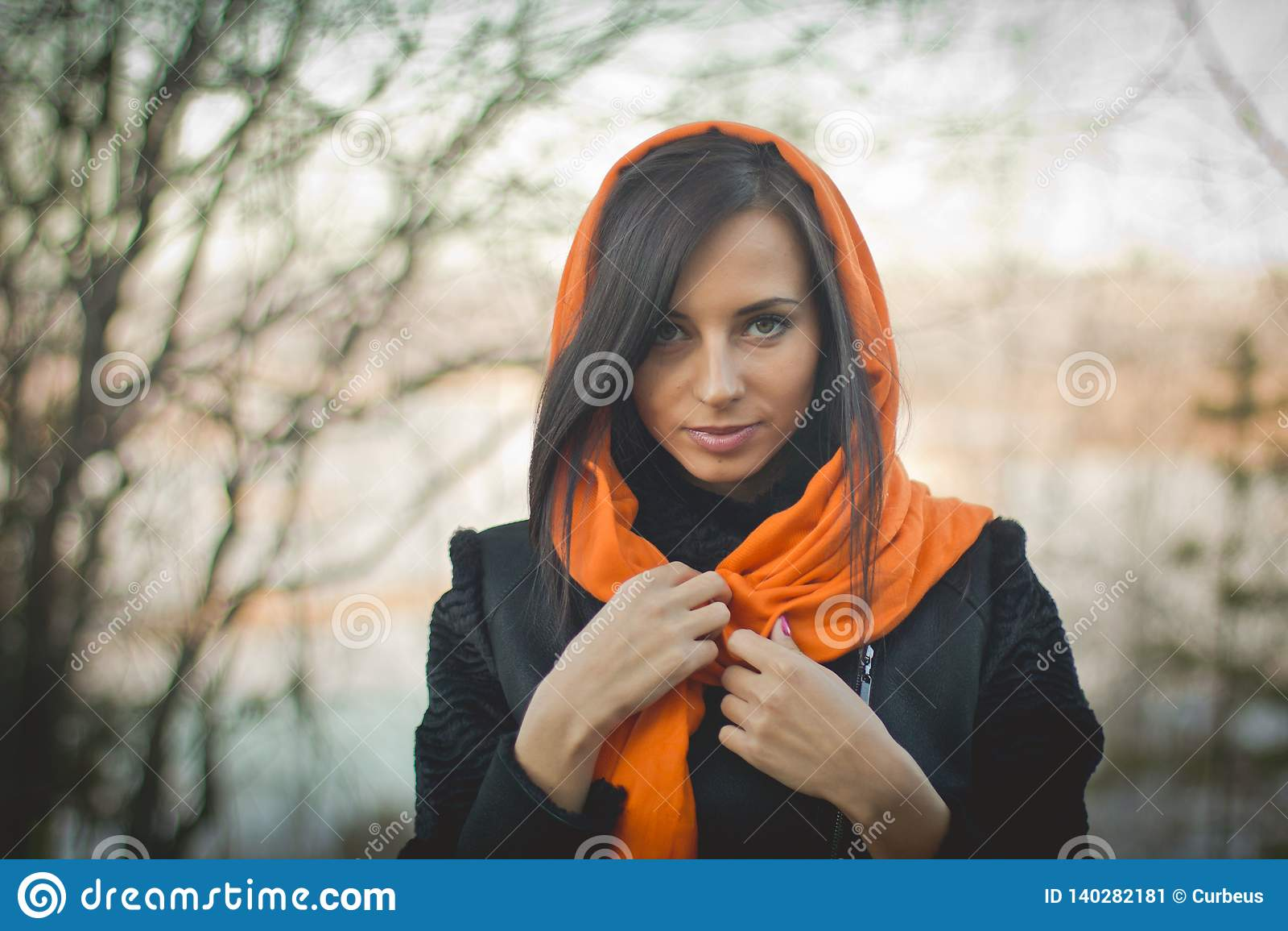 Menina de sorriso no hijab alaranjado na mola de Dubai
