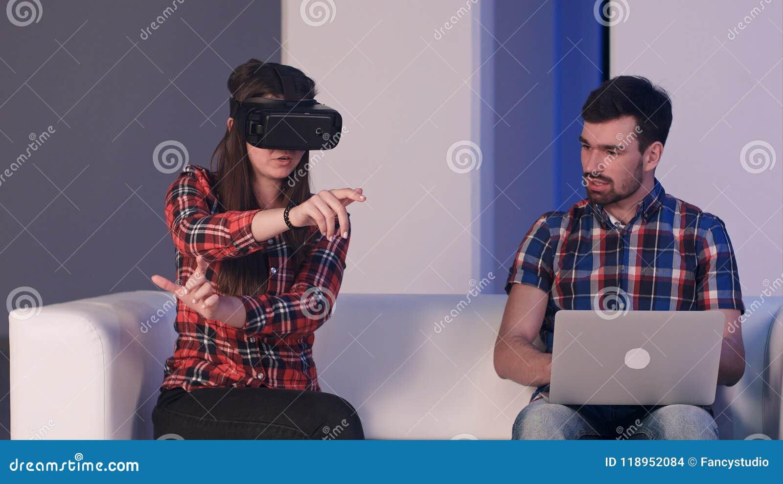 Menina de sorriso nos vidros da realidade virtual que descrevem algo a um homem que senta-se ao lado dela e que datilografa no po