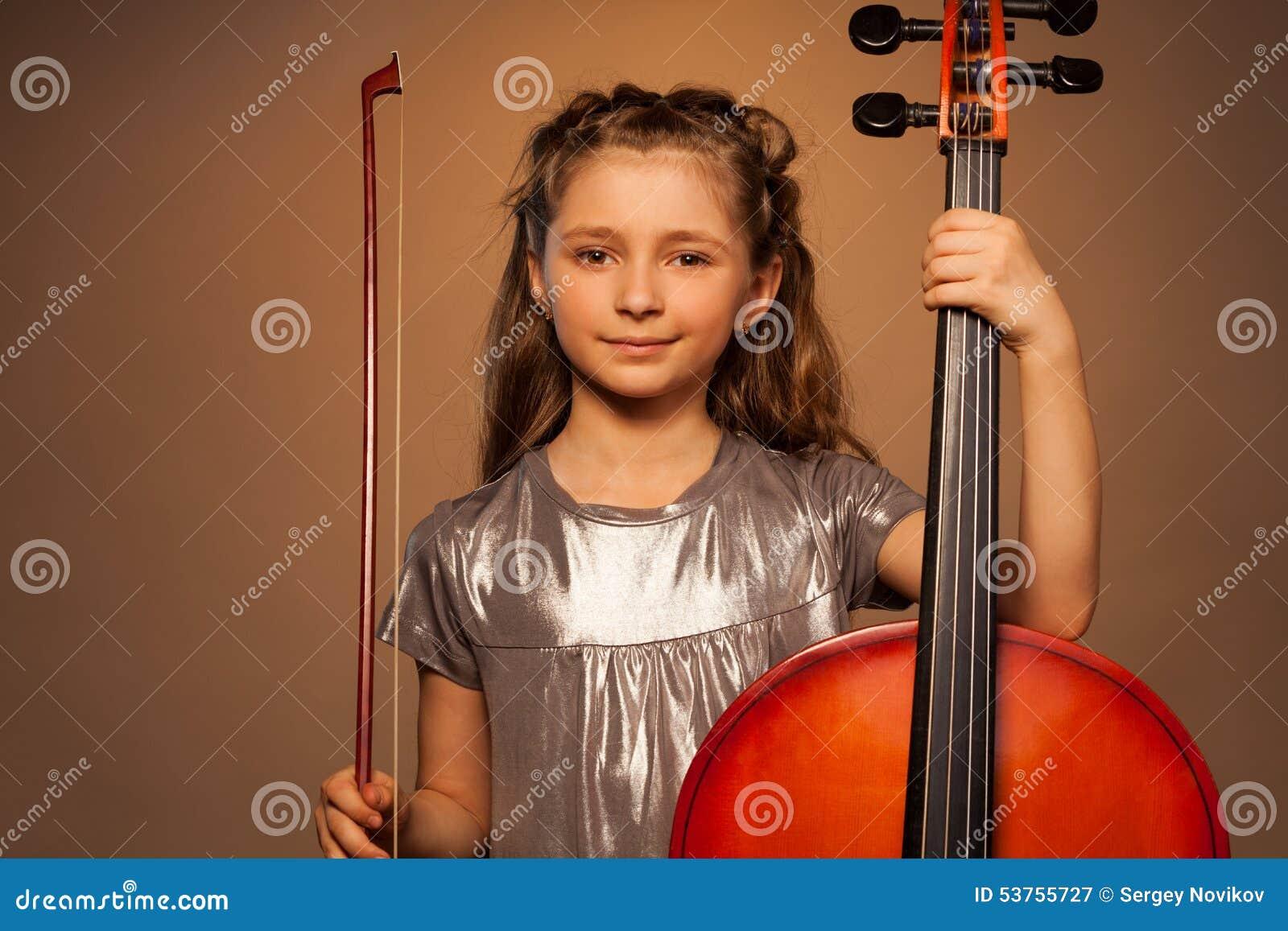 Menina de sorriso que guarda a corda para jogar o violoncelo