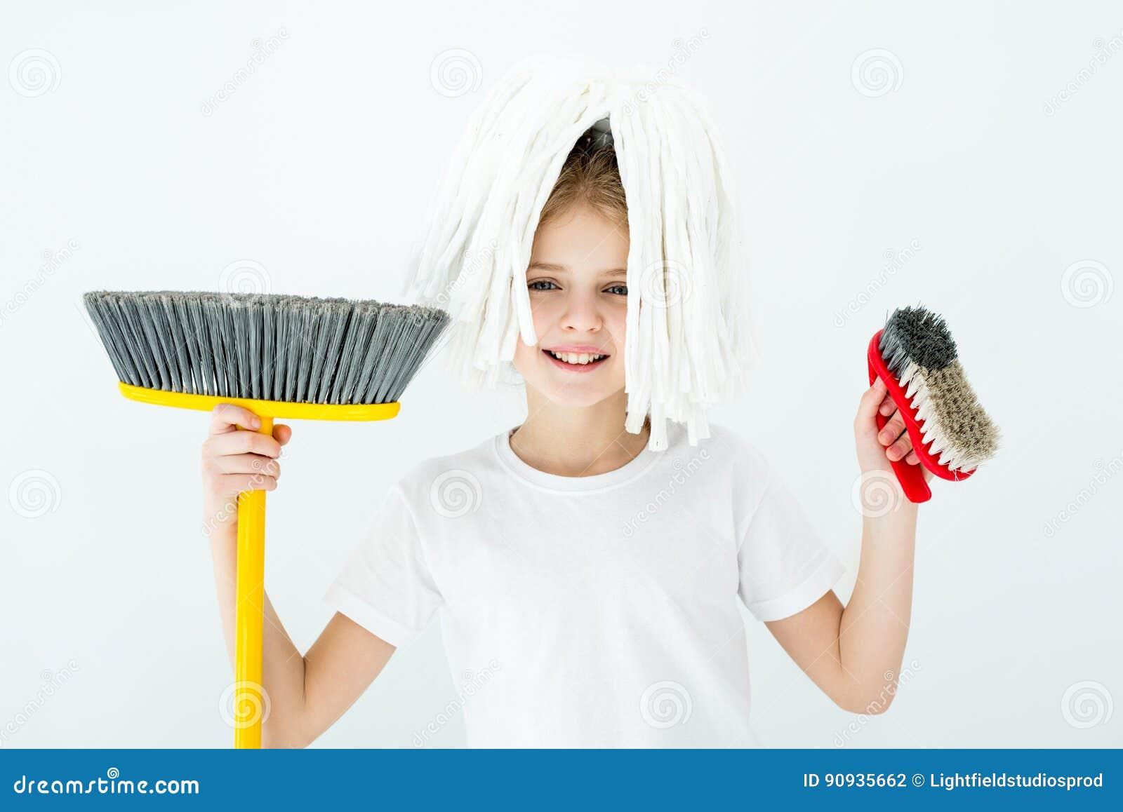 Menina de sorriso que guarda várias fontes de limpeza no branco