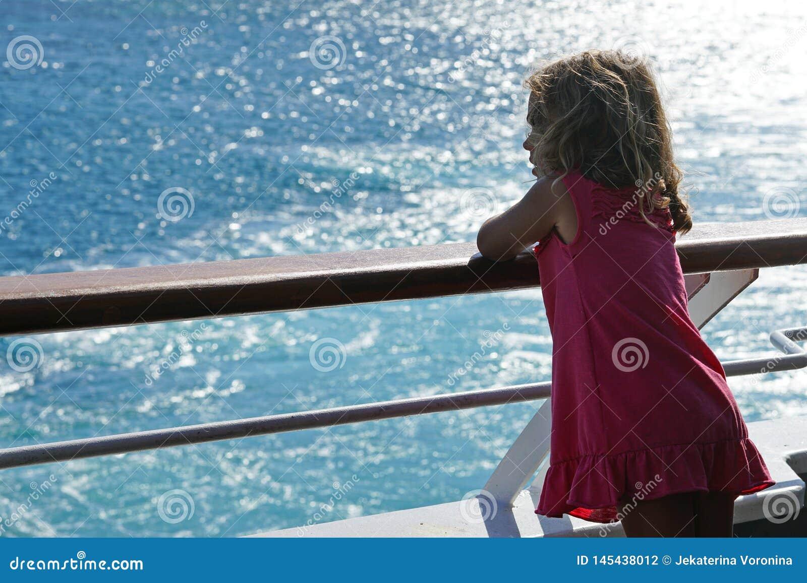 A menina de tr?s anos admira a vista dos Cyclades da balsa