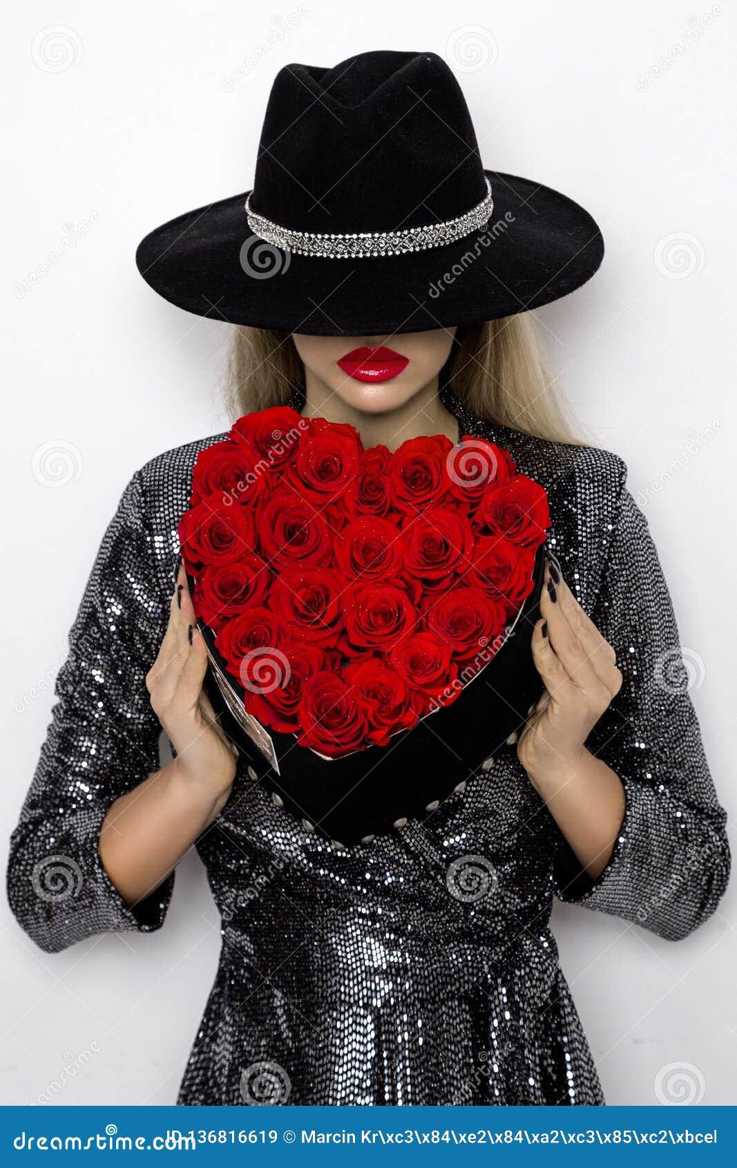 Menina de Valentine Beauty com as rosas vermelhas do coração Retrato de um modelo fêmea novo com presente e chapéu, isolado no fu