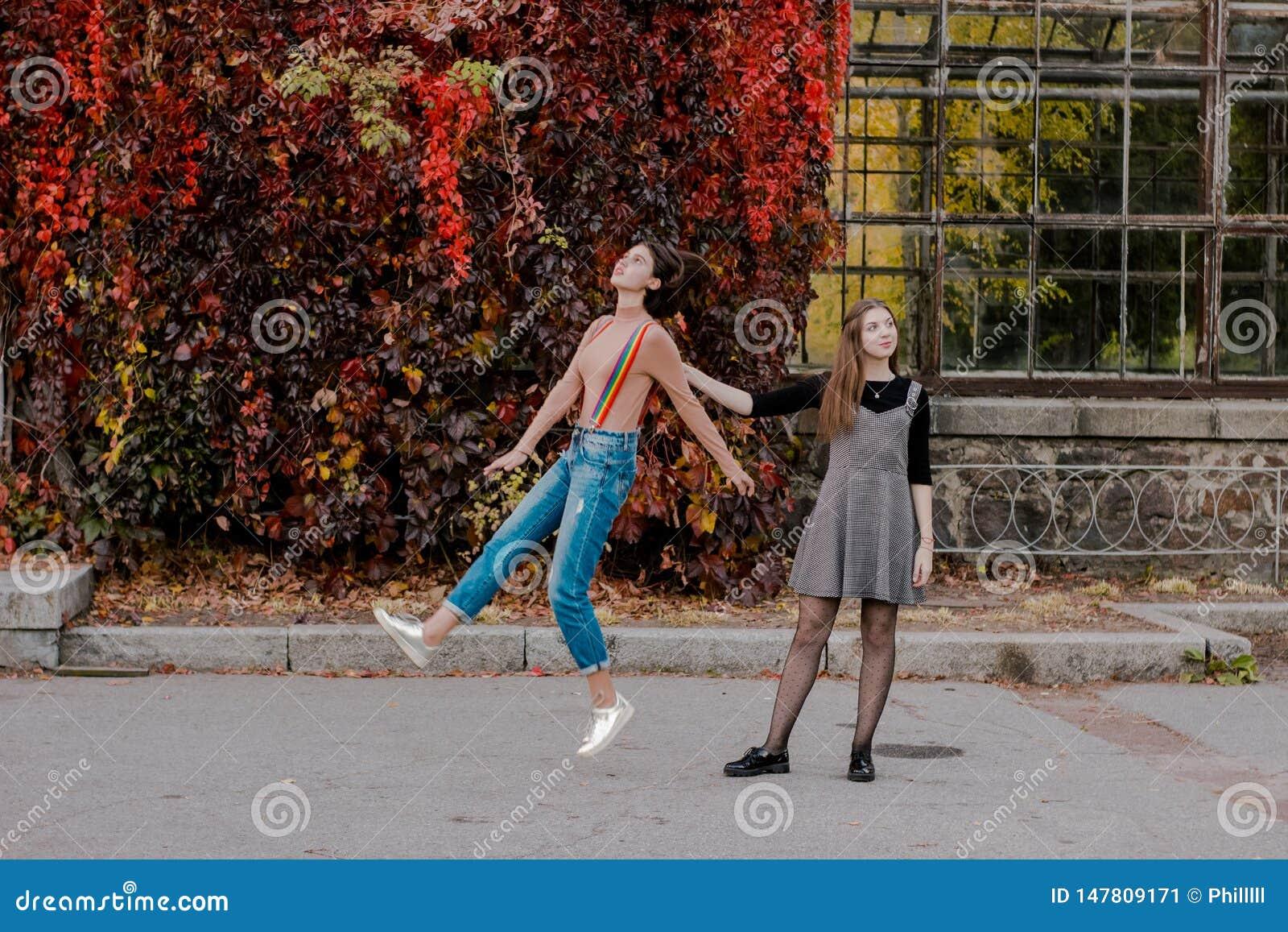 A menina decola ser ao lado da jovem mulher que a mant?m andar no parque do outono