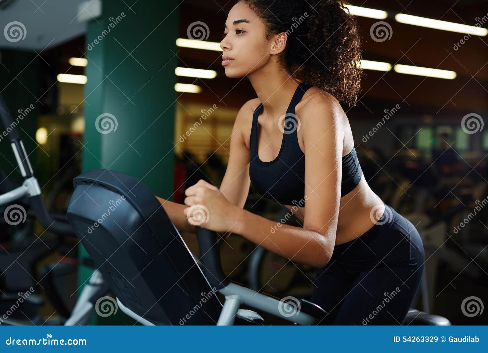 Menina delgada com os bordos sensuais gordos que montam na bicicleta da rotação no fitness center