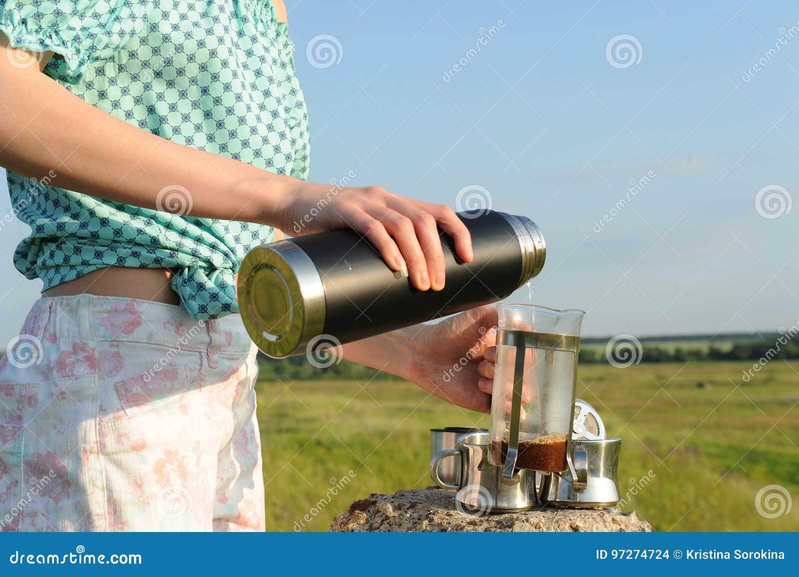 A menina derrama a água a ferver da garrafa térmica na imprensa do francês com café no fundo da paisagem do campo do verão