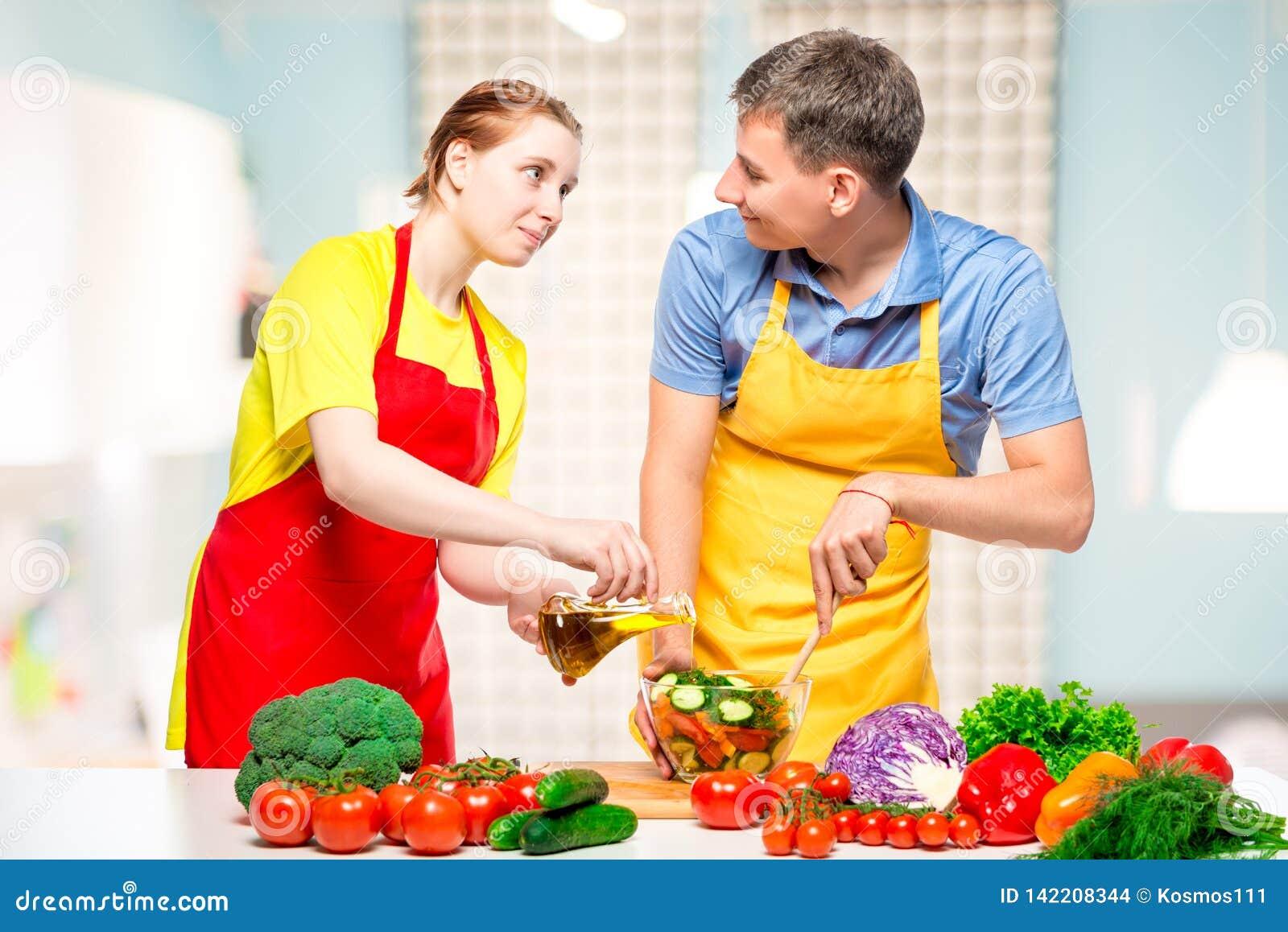 A menina derrama o azeite da salada, família ao cozinhar