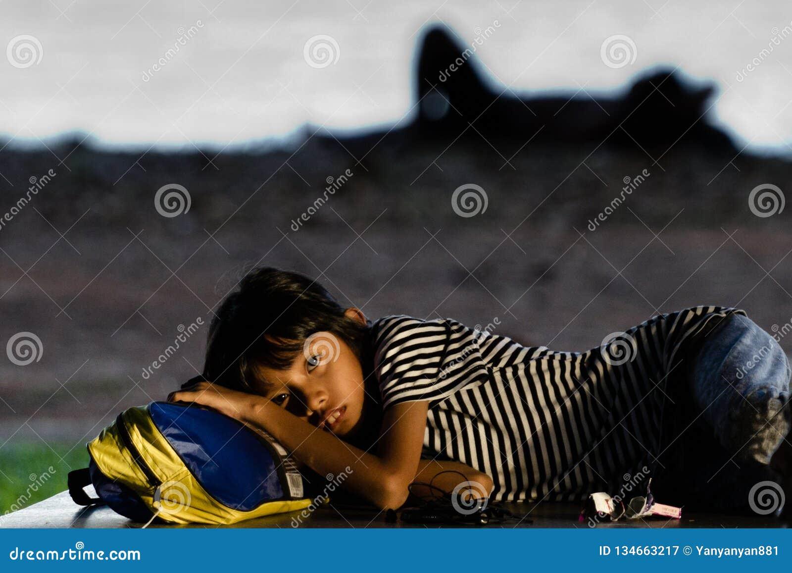 A menina desabrigada coloca em sua trouxa na rua de Singapura