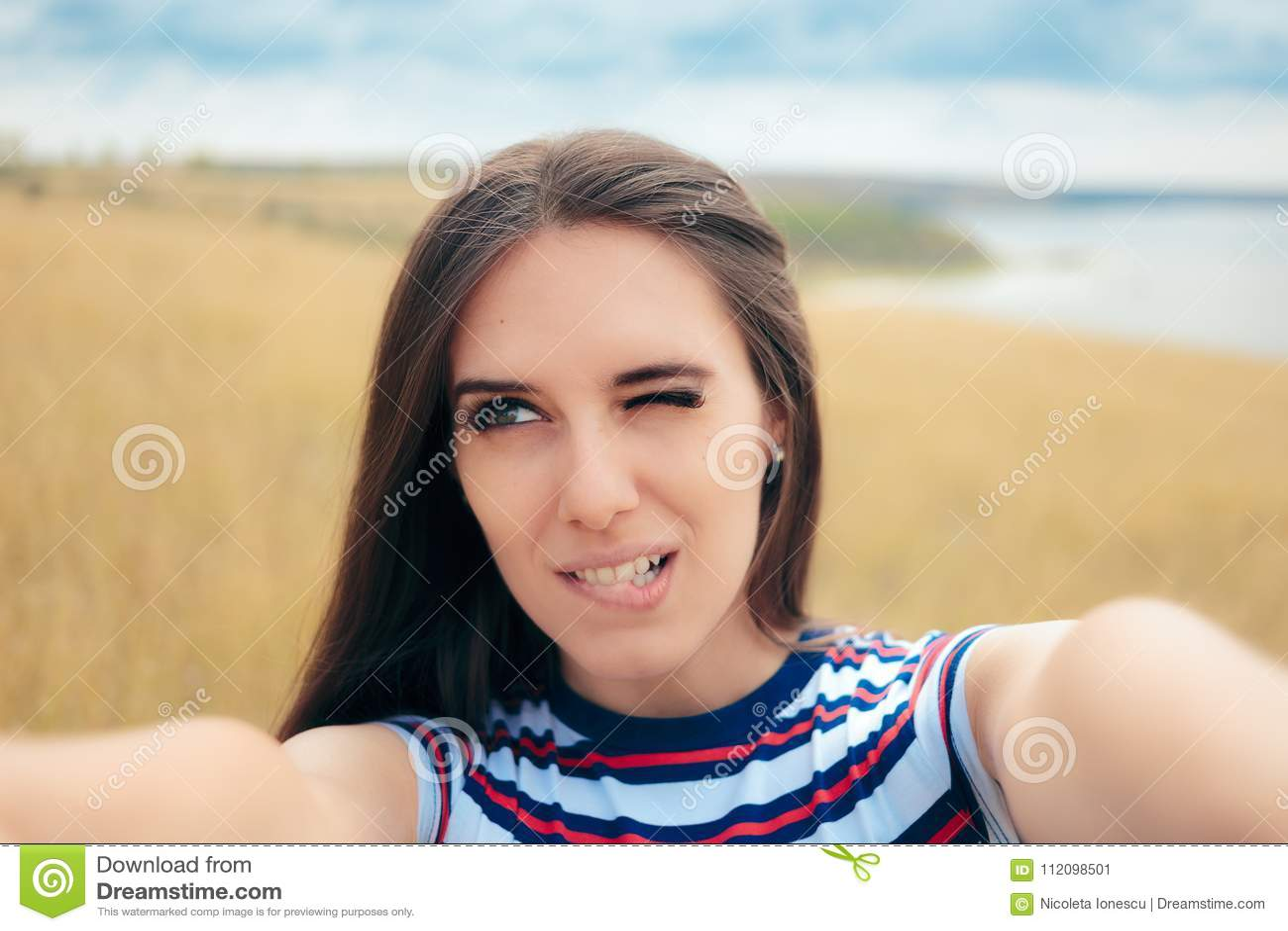 Menina desajeitada que tenta tomar um Selfie na natureza