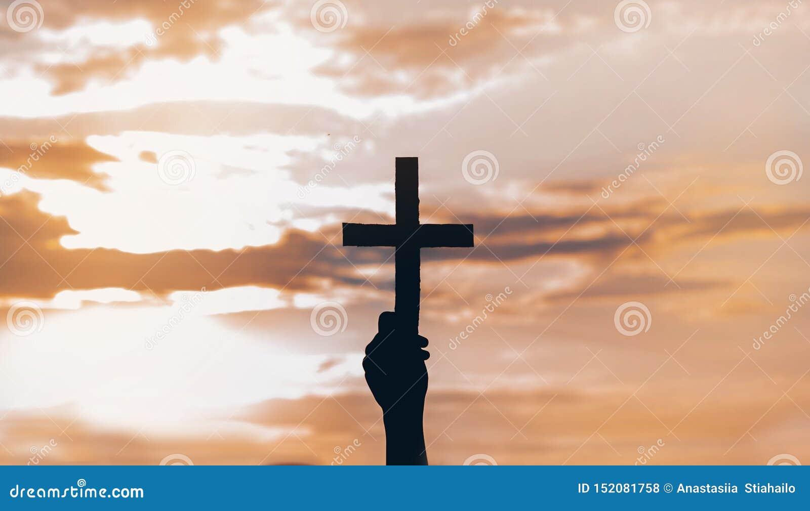 Menina do adolescente guardando a cruz à disposição durante o por do sol bonito M?os dobradas no conceito da ora??o para a f?