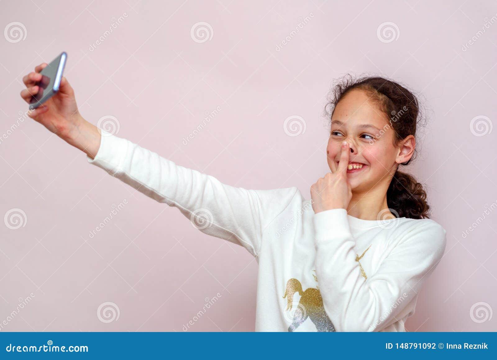 Menina do adolescente que toma o selfie com seu telefone celular no fundo cor-de-rosa