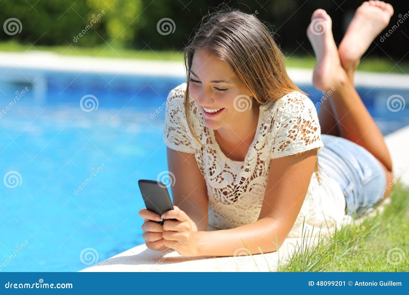 Menina do adolescente que usa um telefone esperto que descansa em um lado da associação