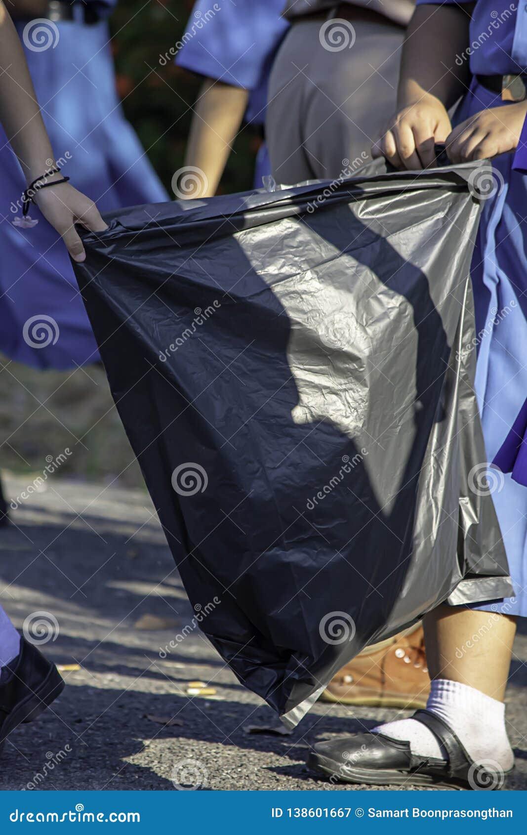 Menina do Asean da mão que guarda sacos de lixo pretos