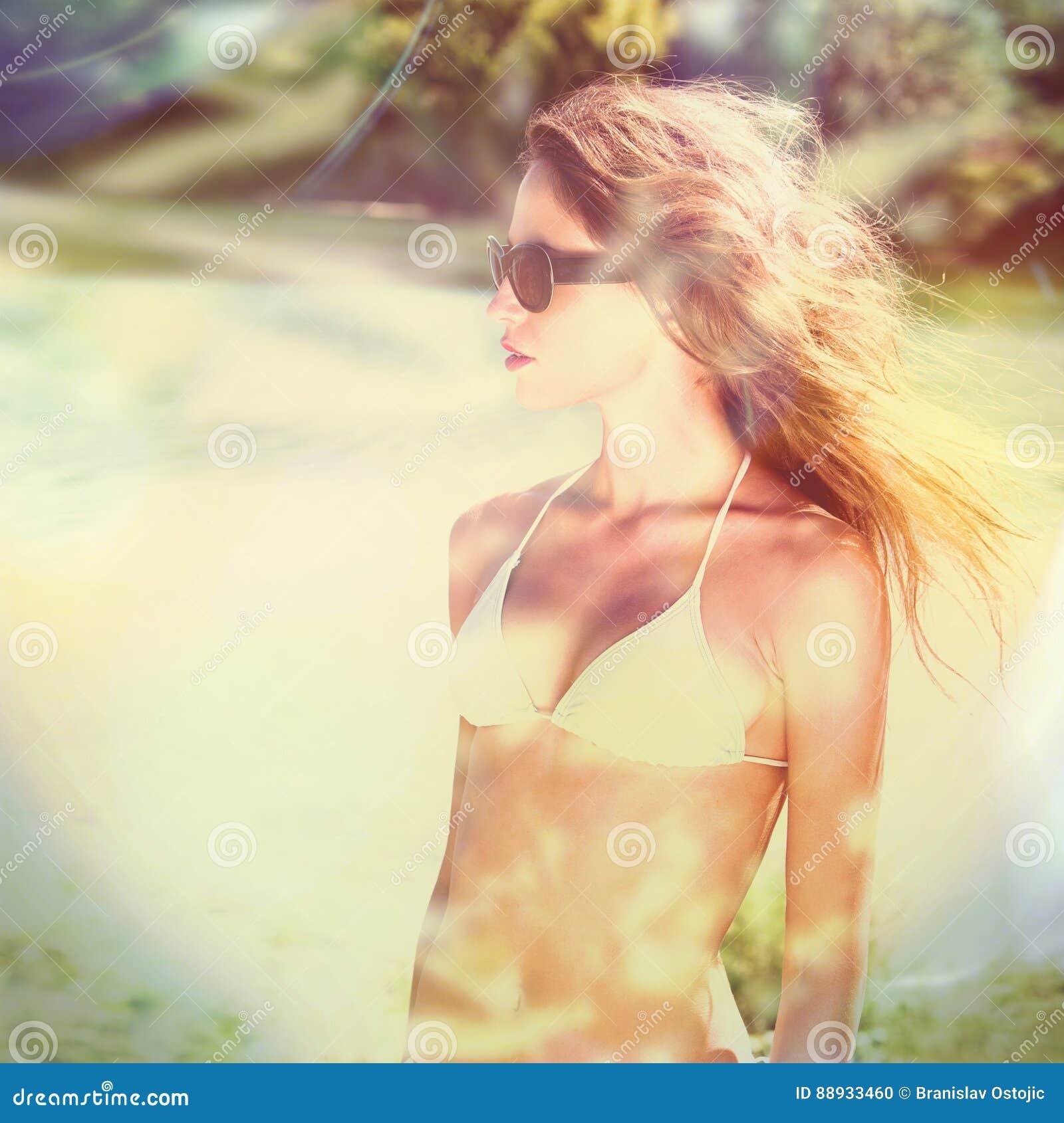 Menina do biquini com as horas de verão dos óculos de sol exteriores