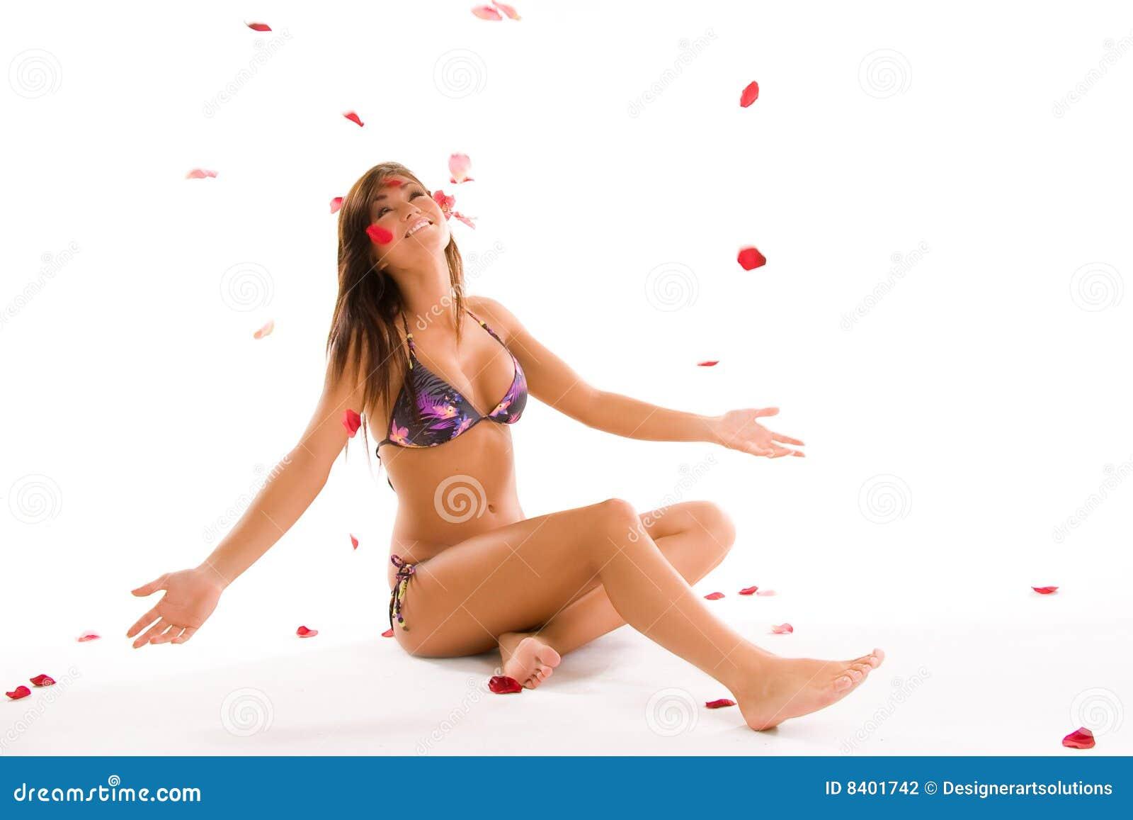 Menina do biquini com pétalas cor-de-rosa