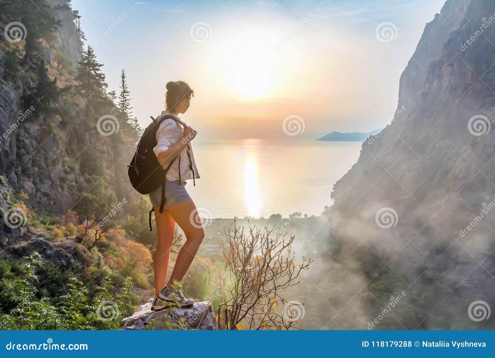 Menina do caminhante na parte superior da montanha