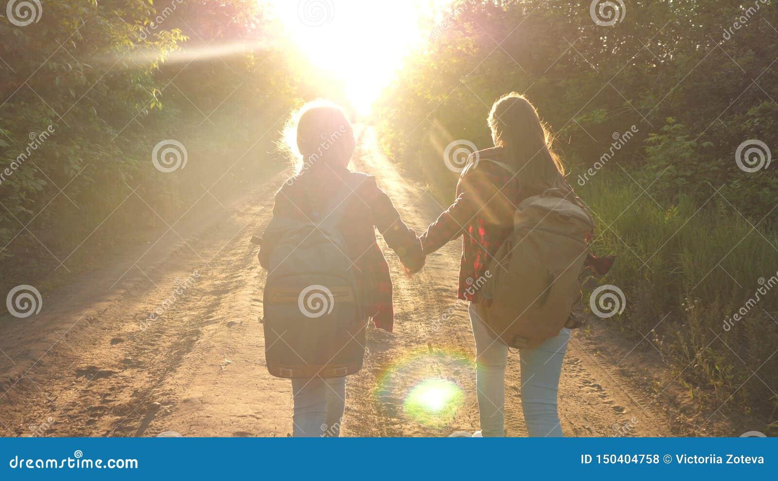Menina do caminhante viajantes felizes das meninas com as trouxas corridas ao longo da estrada secundária que guarda as mãos nos