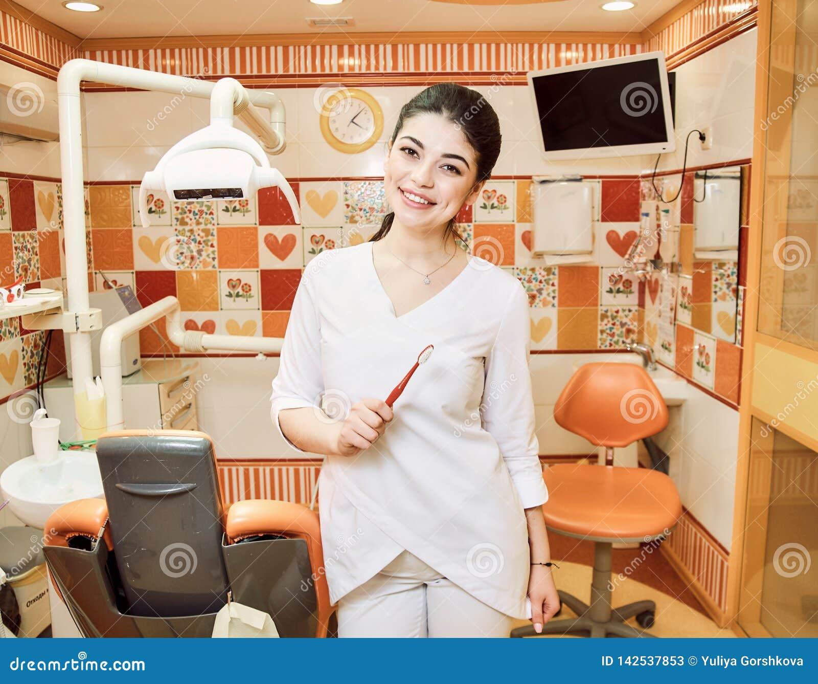 A menina do dentista das crianças no escritório do dentista mantém sua escova de dentes