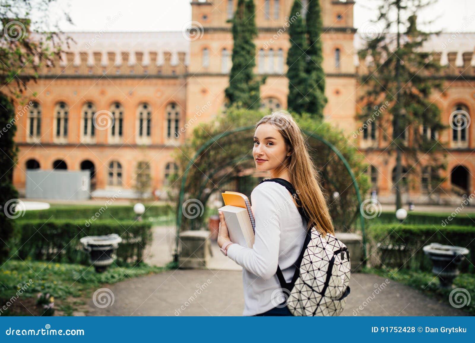 Menina do estudante com o livro em outfoors da universidade
