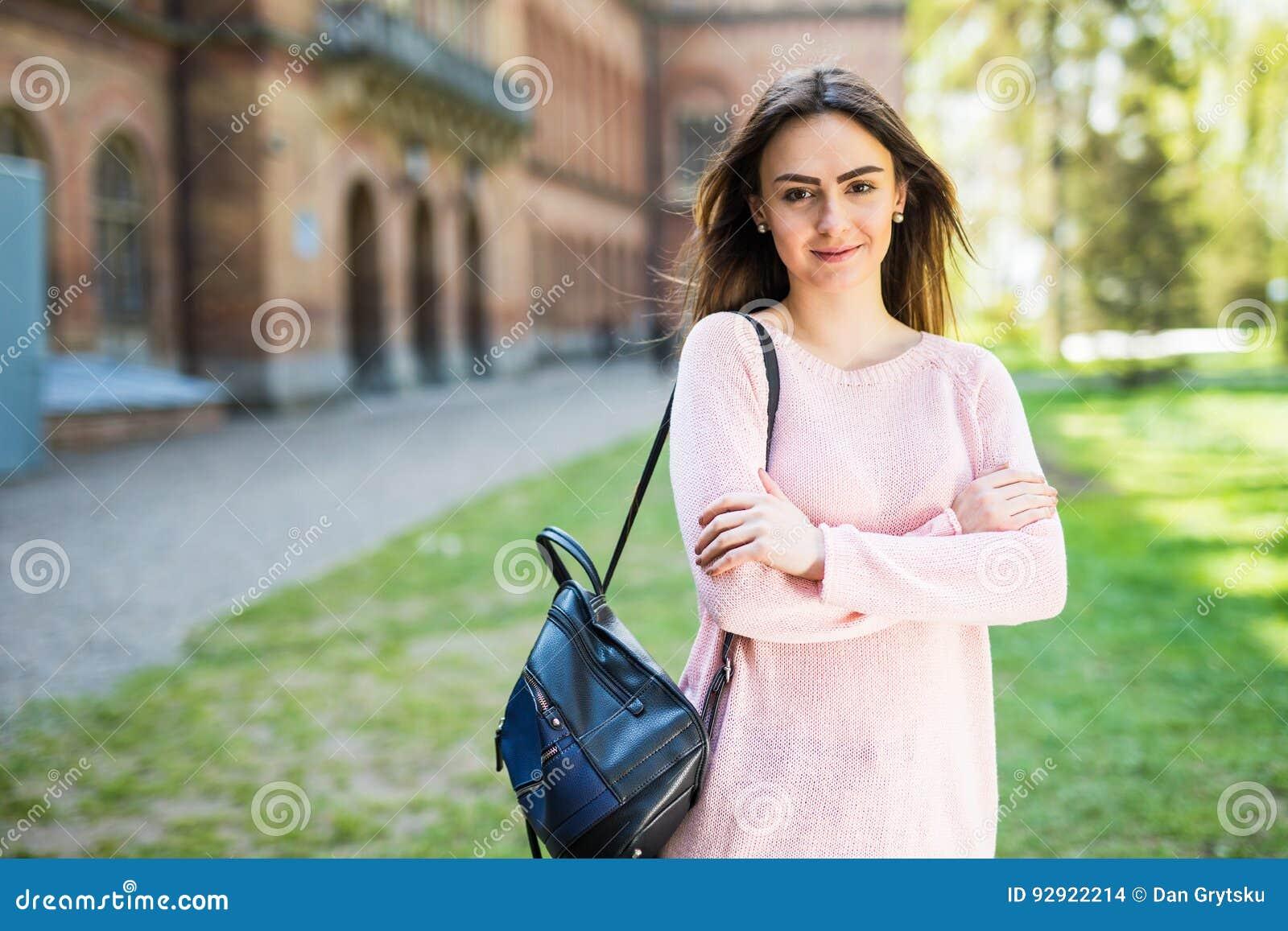 Menina do estudante fora no sorriso do parque do verão feliz Faculdade ou estudante universitário caucasiano Saco de escola vesti