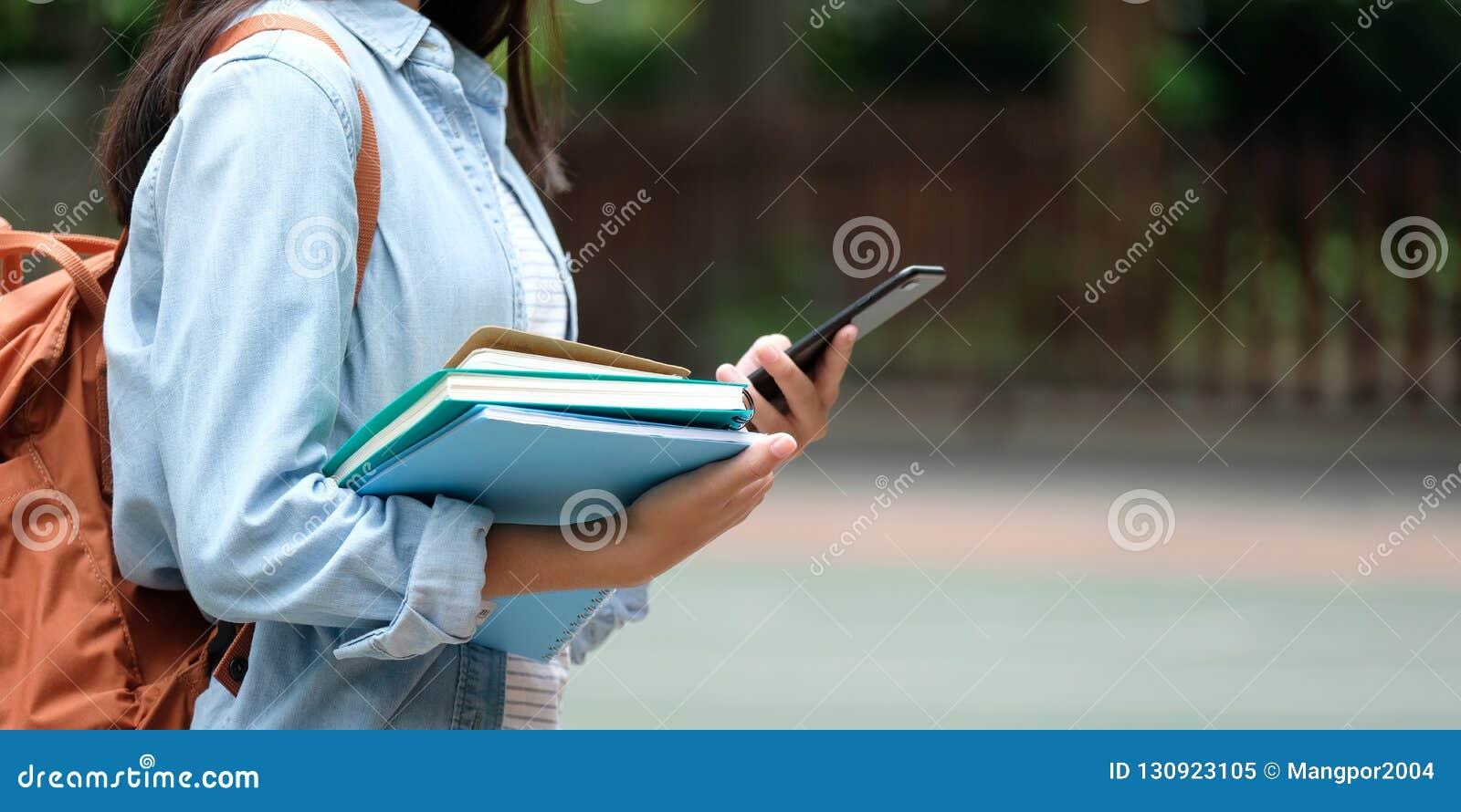 Menina do estudante que guarda livros e smartphone ao andar no schoo