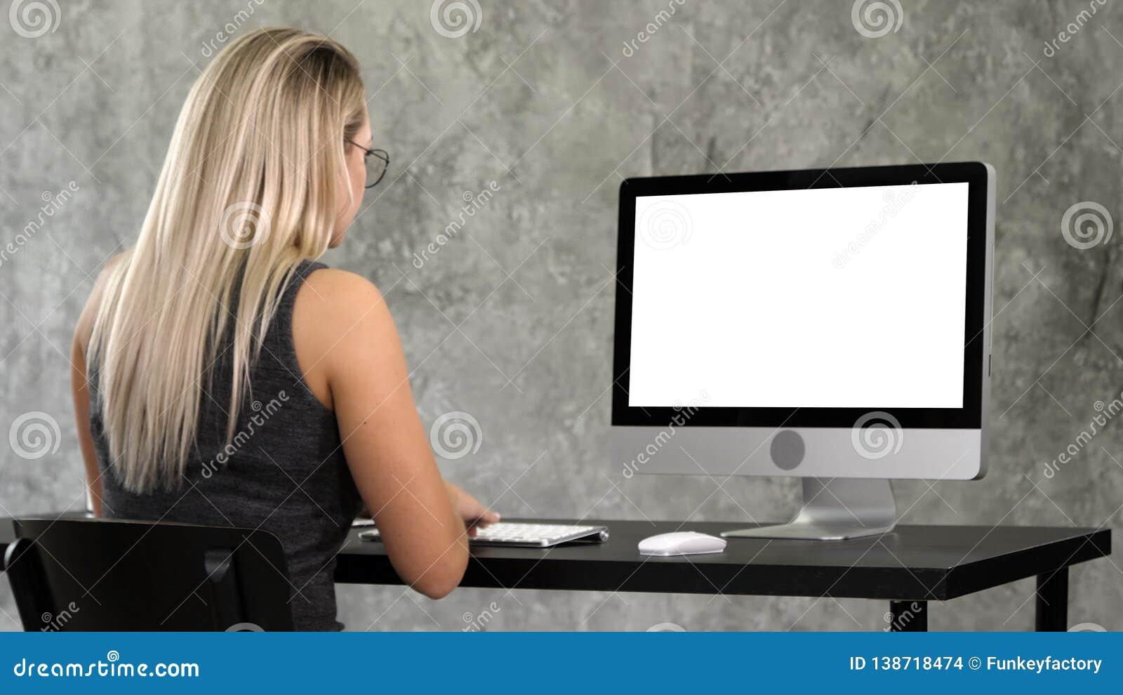 A menina do moderno em vidros na moda senta-se na tabela na frente do funcionamento do computador Indicador branco
