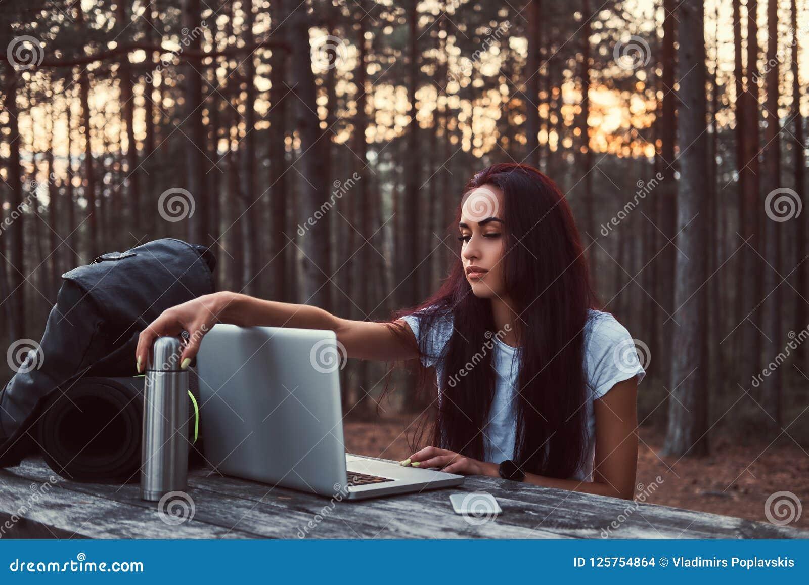 Menina do moderno que trabalha em um portátil em um banco de madeira ao ter uma ruptura na floresta bonita do outono