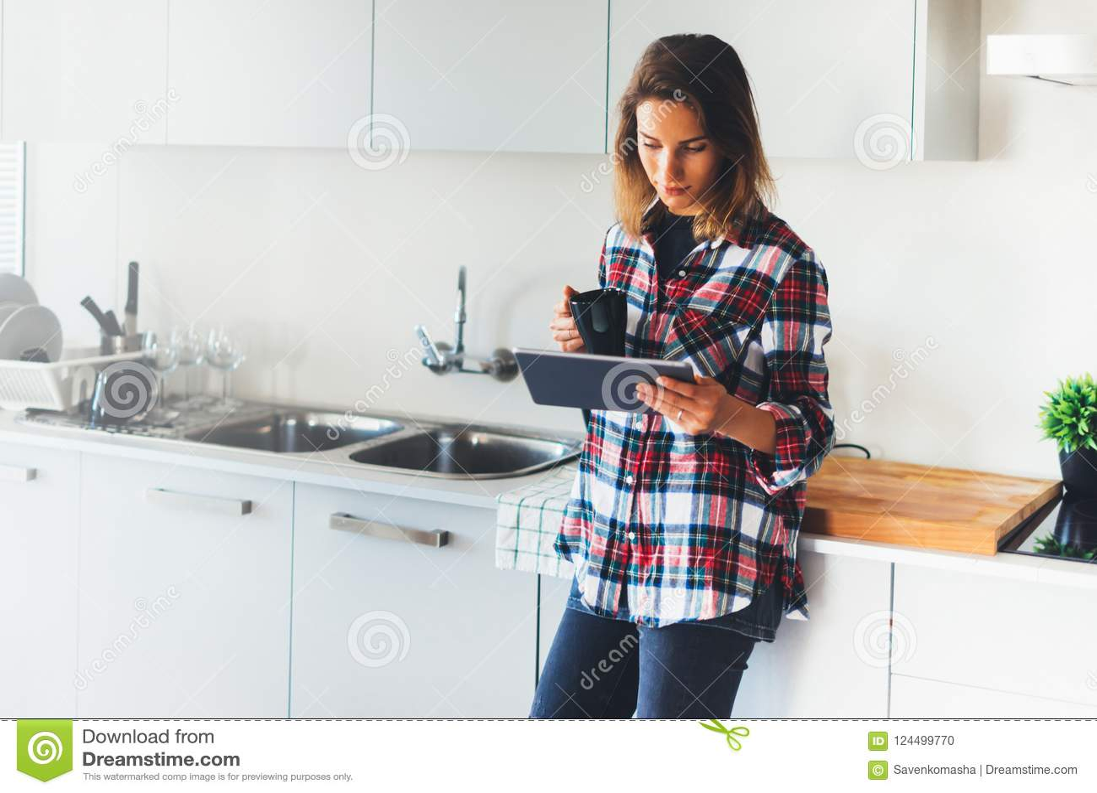 Menina do moderno que usa o café da tecnologia e da bebida da tabuleta na cozinha,
