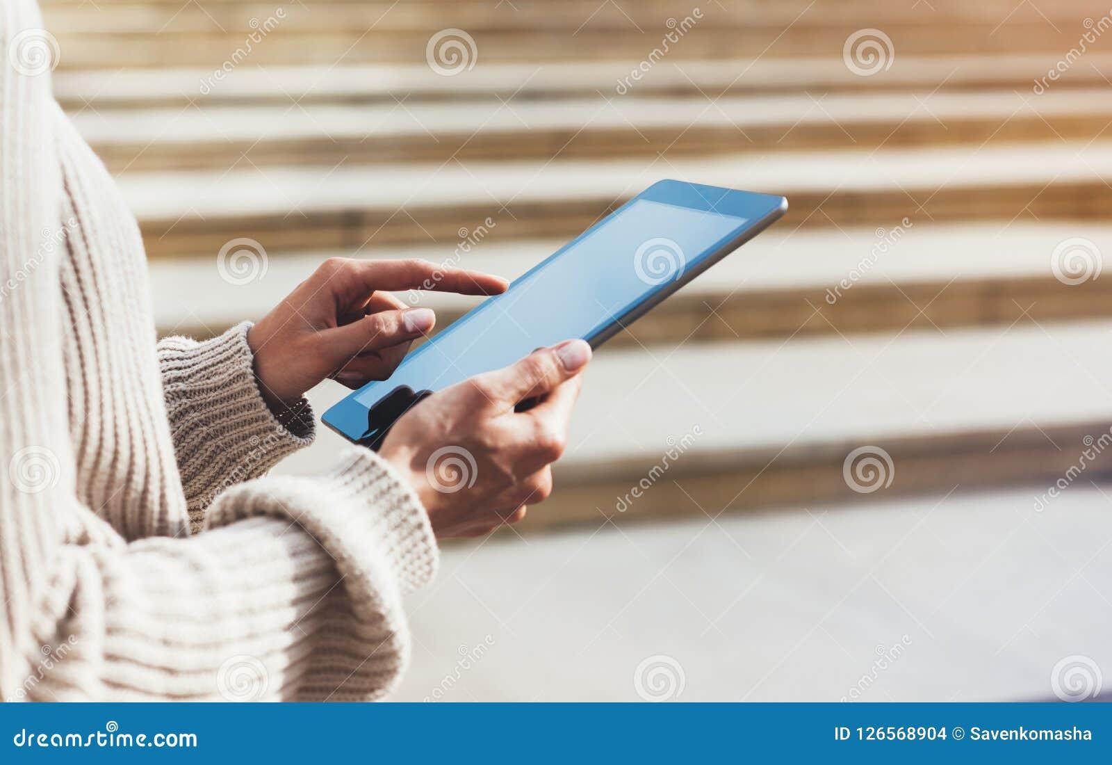 Menina do moderno que usa o Internet da tecnologia da tabuleta, pessoa do blogger que guarda o computador no fundo Sun City, mãos