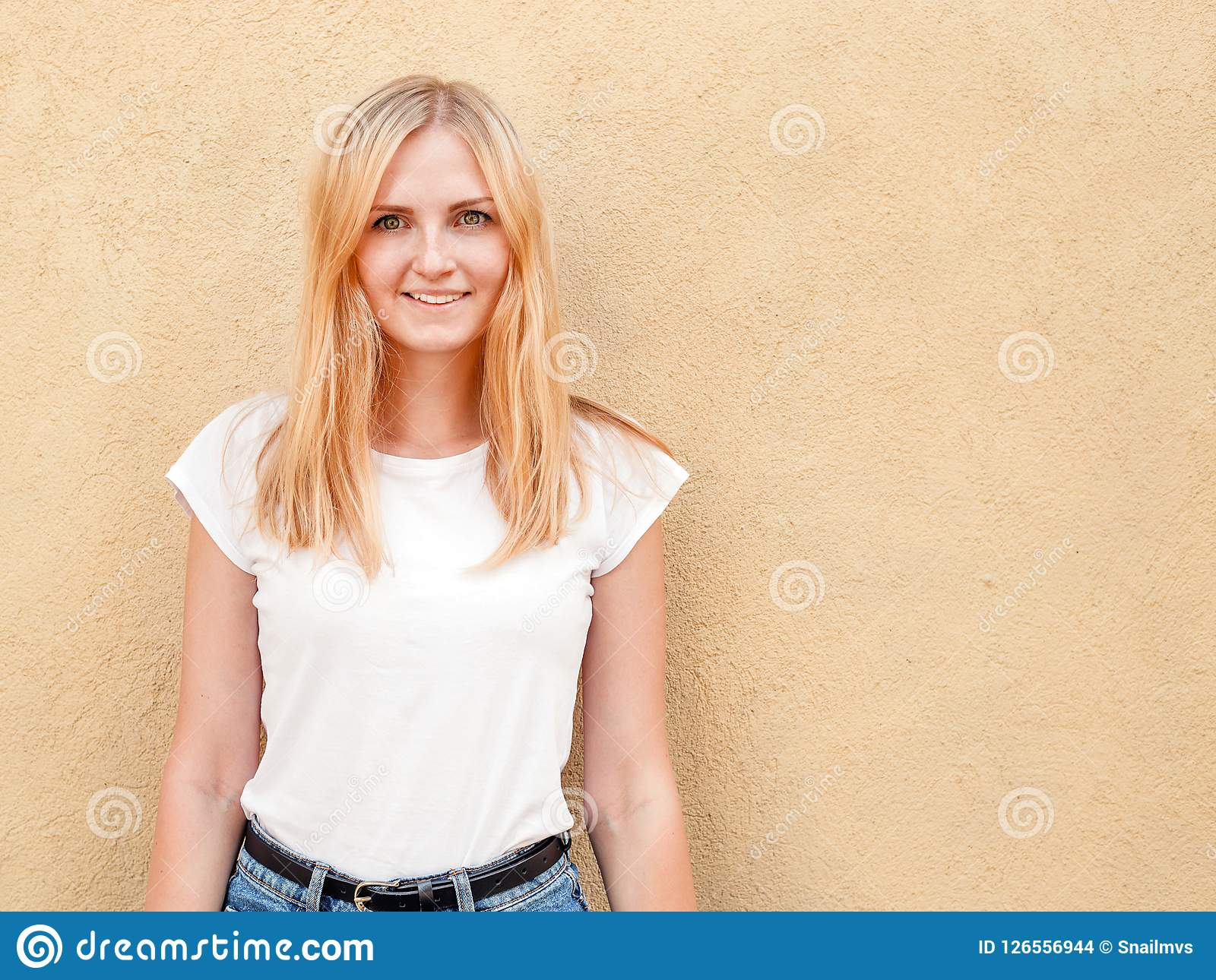 Menina do moderno que veste o t-shirt vazio e as calças de brim brancos que levantam contra a parede áspera da rua, estilo urbano