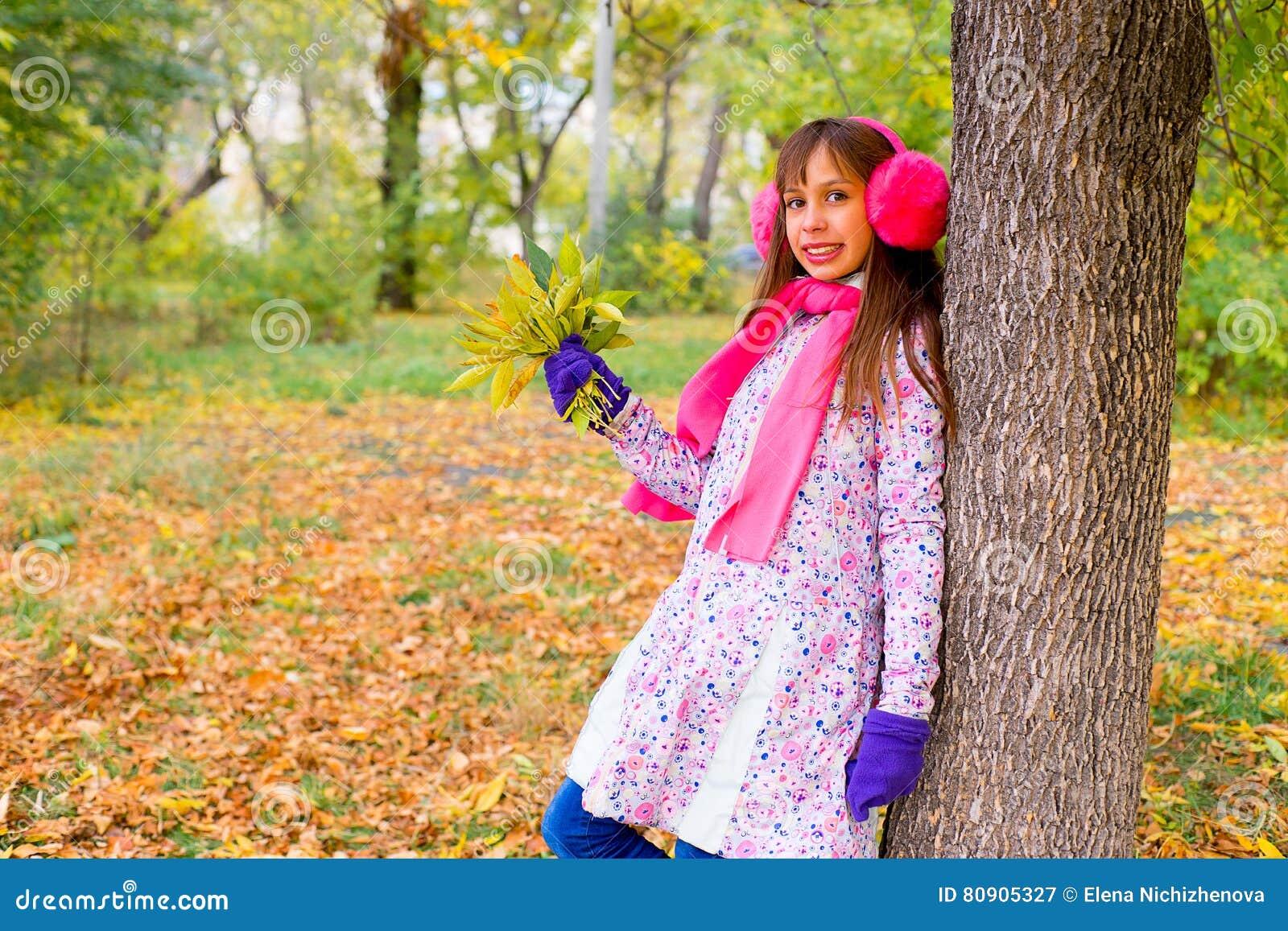 Menina do Preteen no parque do outono com folhas