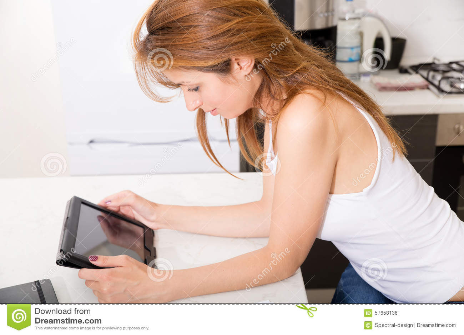 Menina do ruivo que guarda o PC da tabuleta na cozinha