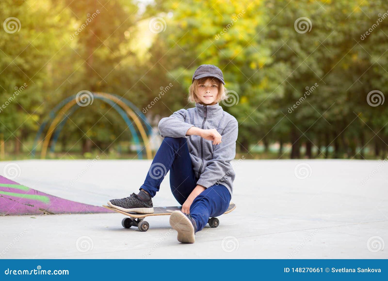 Menina do skater no skatepark que move sobre o skate fora