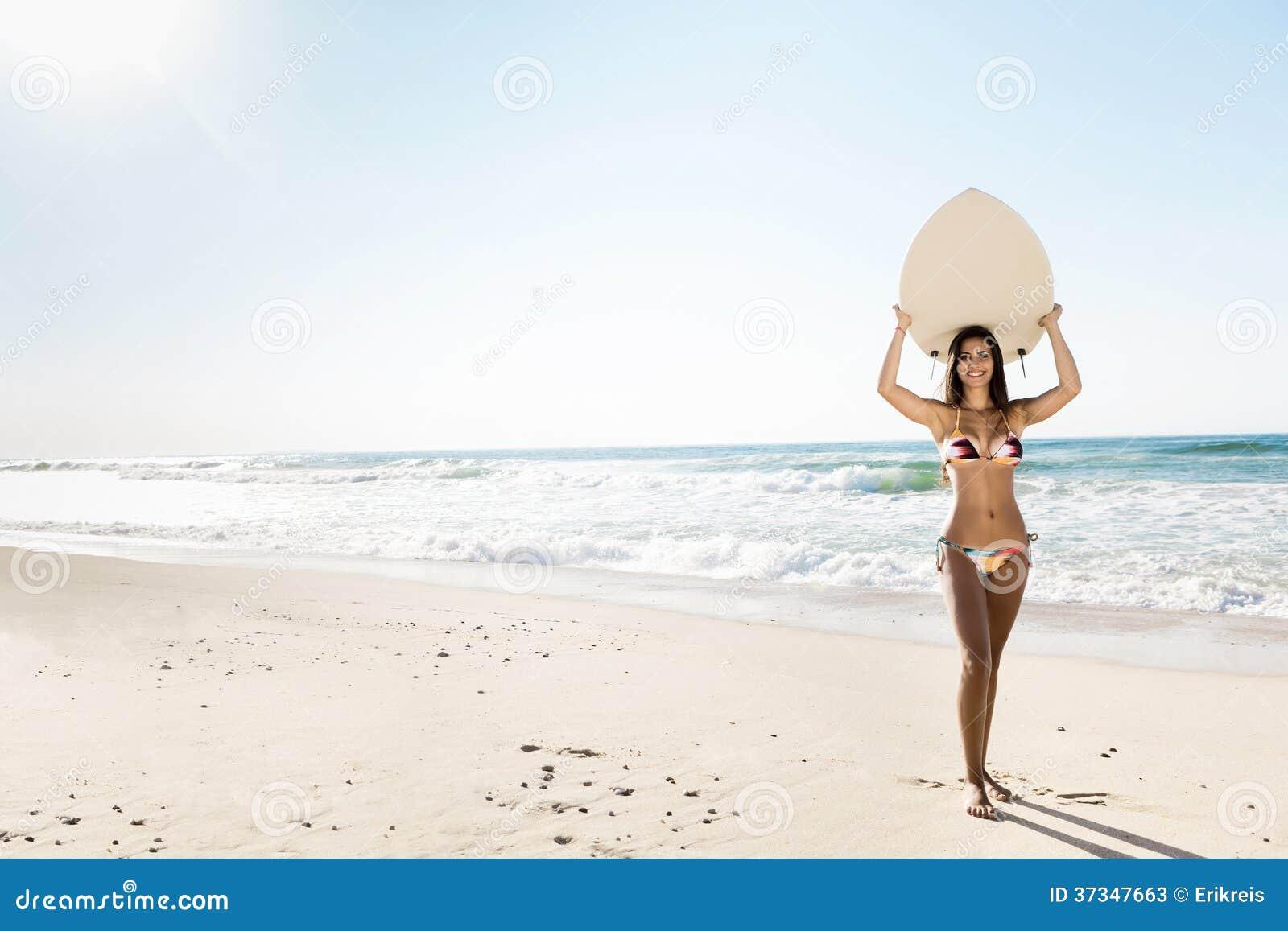 Menina do surfista com sua prancha