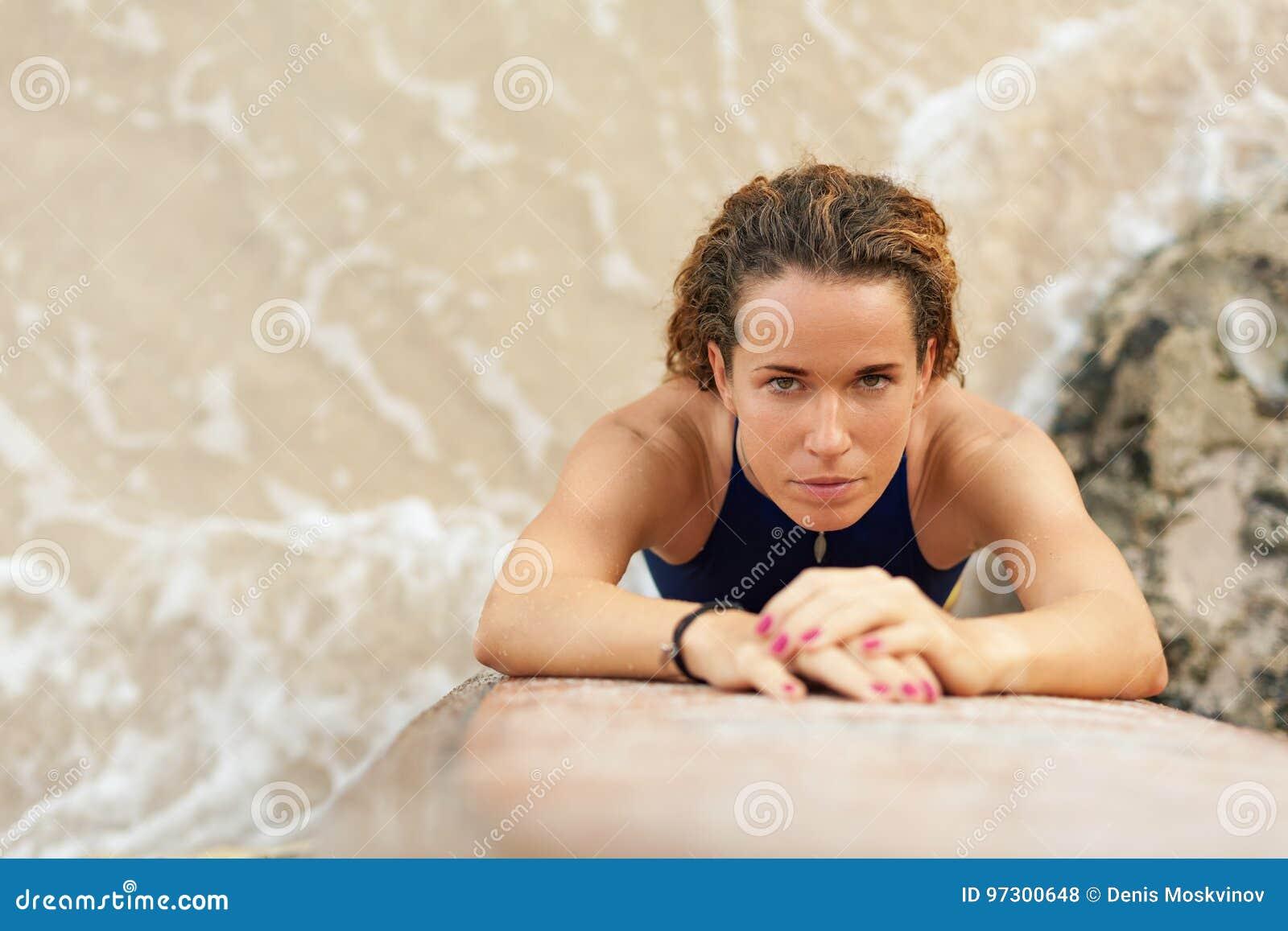 Menina do surfista do retrato no biquini com a prancha na praia