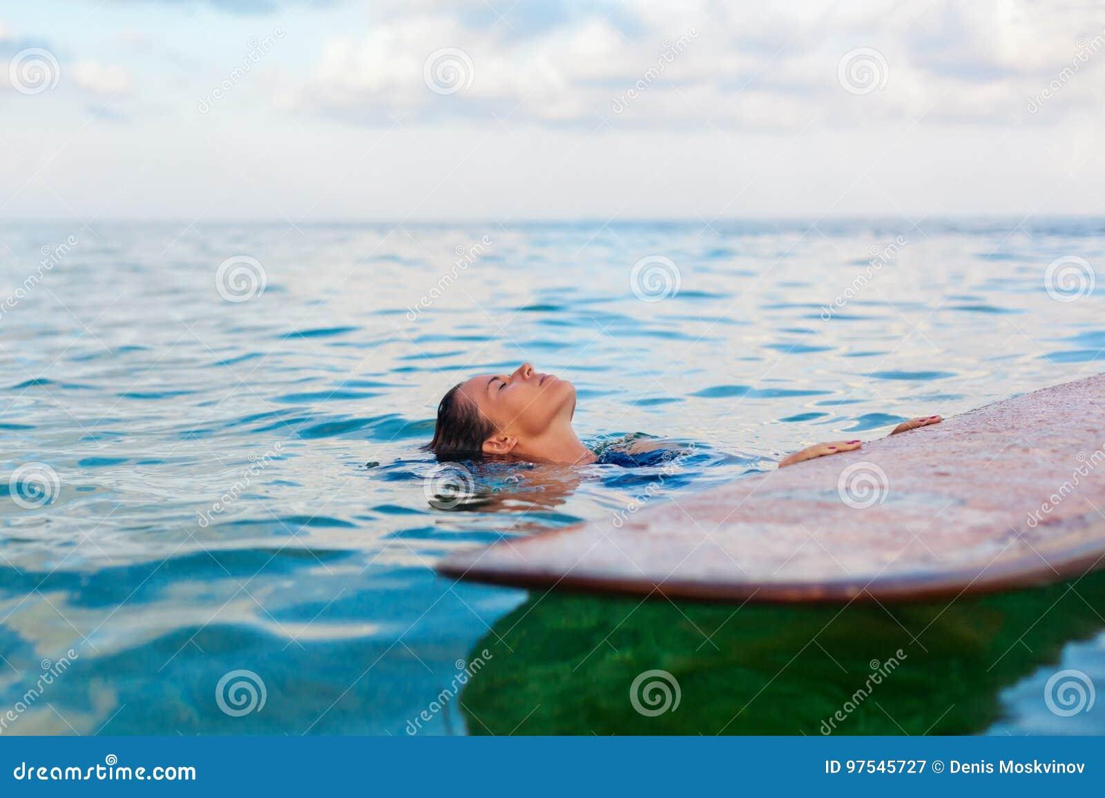 A menina do surfista na prancha tem um divertimento antes de surfar
