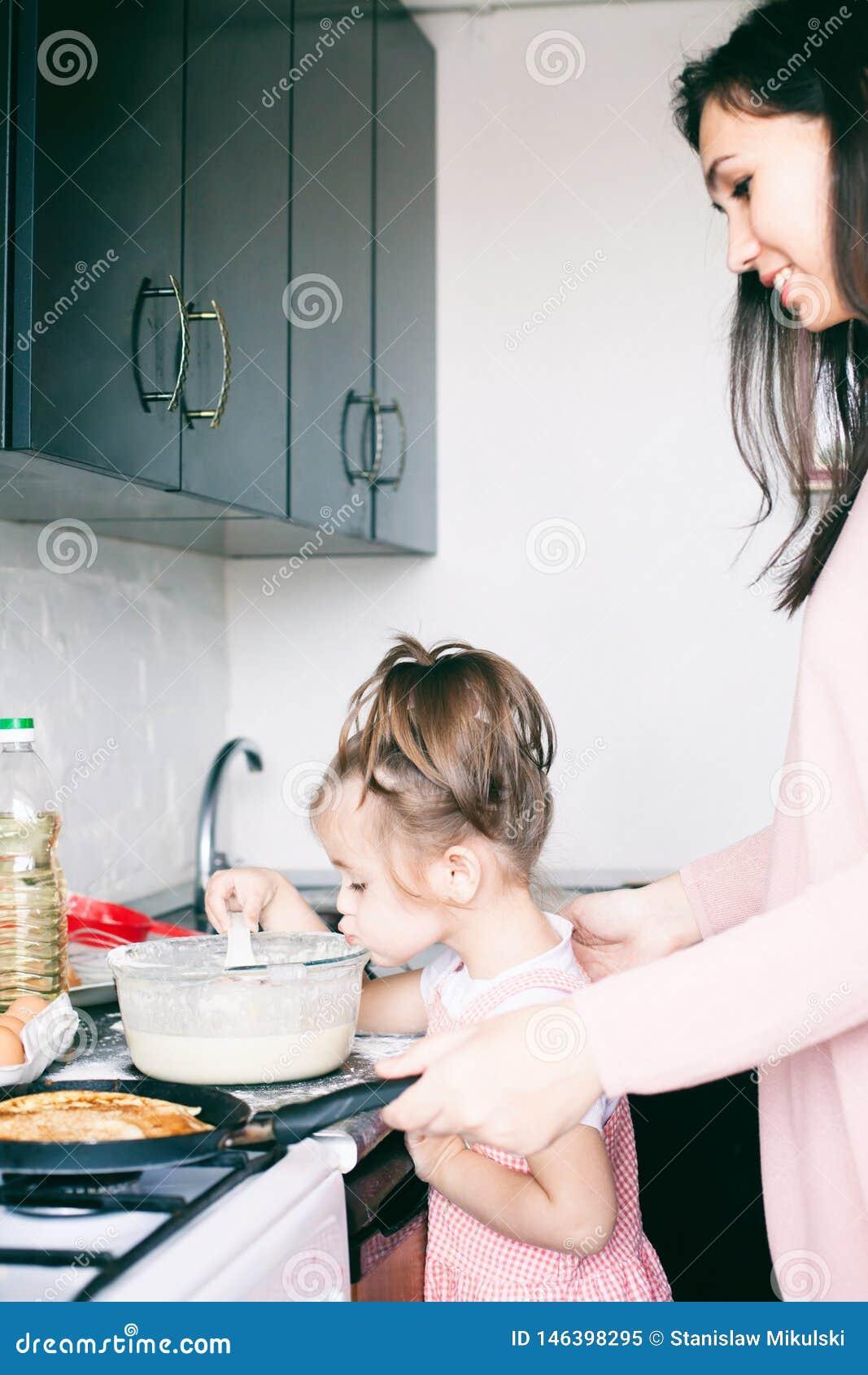 Menina doce pequena e suas panquecas da fritada da m?e no carnaval tradicional Maslenitsa Shrovetide do feriado do russo
